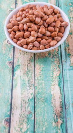 earthnuts: Ground nut or peanuts in white bowl over weathered wooden background
