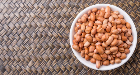 Ground nut or peanuts in white bowl over wicker background Stock Photo