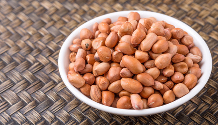 ground nut: Ground nut or peanuts in white bowl over wicker background Stock Photo