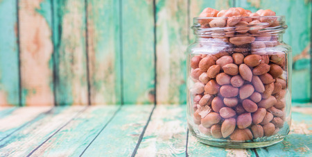ground nut: Ground nut or peanuts in a mason jar over weathered wooden background Stock Photo