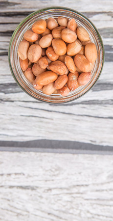 earthnuts: Ground nut or peanuts in a mason jar over weathered wooden background Stock Photo