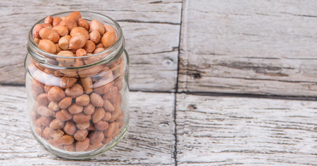 Ground nut or peanuts in a mason jar over weathered wooden background Stock Photo