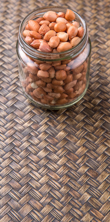 ground nut: Ground nut or peanuts in a mason jar over wicker background