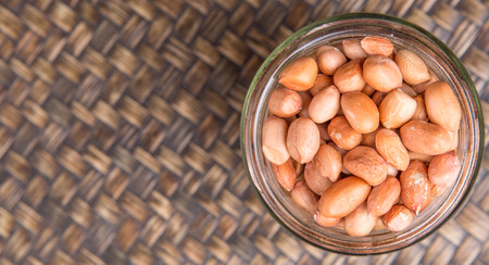 earthnuts: Ground nut or peanuts in a mason jar over wicker background