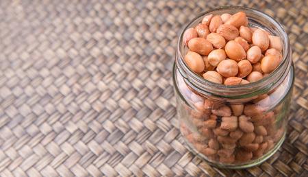 ground nut: Ground nut or peanuts in a mason jar over wicker background