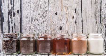 creamer: Coffee beans, coffee powder, creamer, cocoa powder, honey and processed tea leaves in a mason jar over weathered wooden background Stock Photo