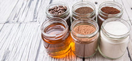 creamer: Coffee beans, coffee powder, creamer, cocoa powder, honey and processed tea leaves in mason jars over weathered wooden background