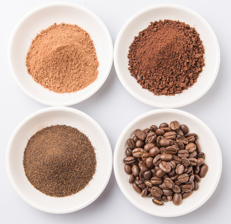 chocolate powder: Coffee beans, powdered coffee, chocolate powder and processed tea leaves beverages in white bowls over white background Stock Photo