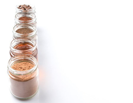 chocolate powder: Coffee beans, powdered coffee, honey, chocolate powder and processed tea leaves beverages in mason jar  over white background Stock Photo