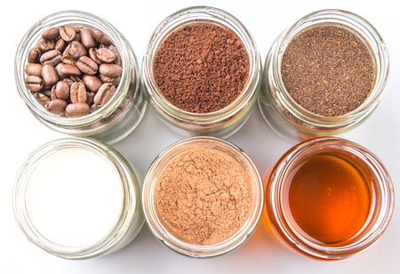creamer: Coffee beans, coffee powder, creamer, cocoa powder, honey and processed tea leaves in mason jars over white background Stock Photo