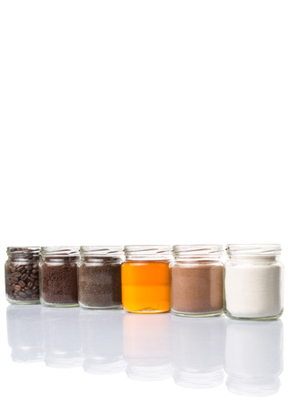 creamer: Coffee beans, coffee powder, creamer, cocoa powder, honey and processed tea leaves in a mason jar over white background