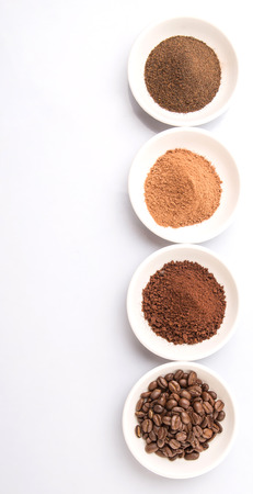 cocoa powder: Coffee beans, powdered coffee, chocolate powder and processed tea leaves beverages in white bowls over white background Stock Photo