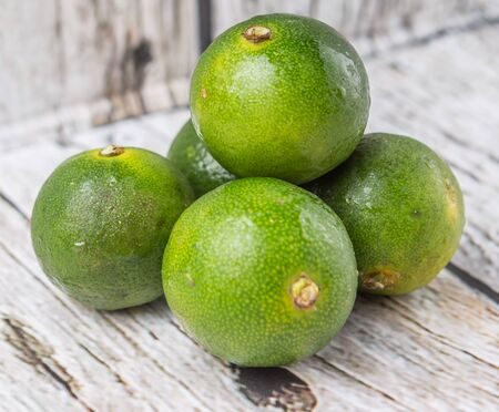Calamansi citrus over weathered wooden background