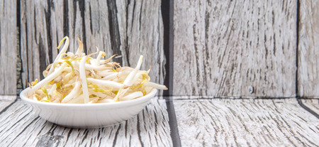 bean sprouts: Bean sprouts in white bowl over weathered wooden background