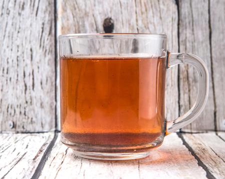 astringent: A mug of tea over weathered wooden background