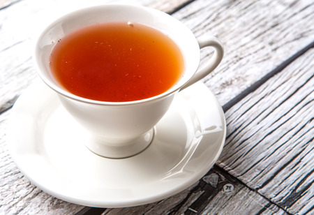 astringent: A cup of tea over weathered wooden background