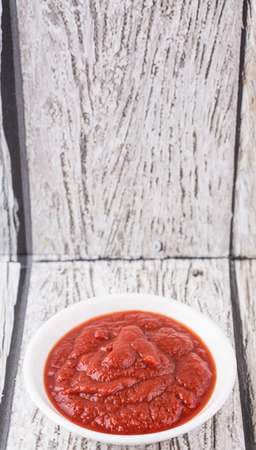 pureed: Fresh pureed tomato in white bowl over rustic wooden background