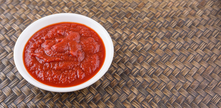 pureed: Fresh pureed tomato in white bowl over wicker background