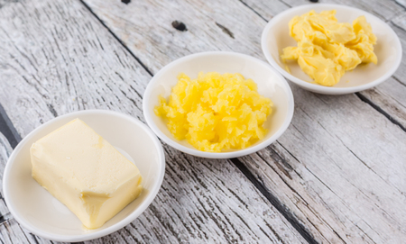 ghee: A block of butter, margarine and ghee in white bowls over rustic wooden background