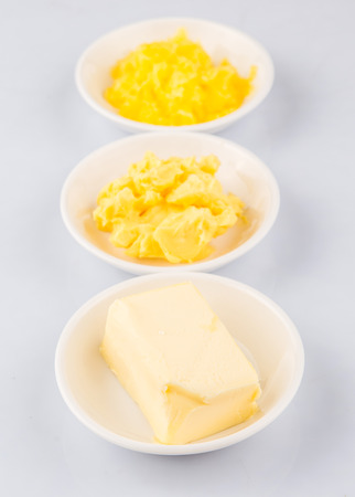 ghee: A block of butter, margarine and ghee in white bowls