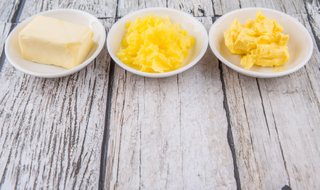 margarine: A block of butter, margarine and ghee in white bowls over rustic wooden background