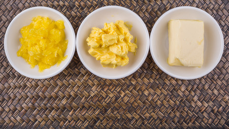 margarine: A block of butter, margarine and ghee in white bowls over wicker background Stock Photo