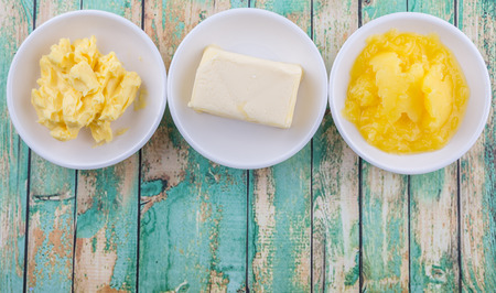 A block of butter, margarine and ghee in white bowls over rustic wooden background