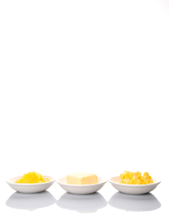 margarine: A block of butter, margarine and ghee in white bowls