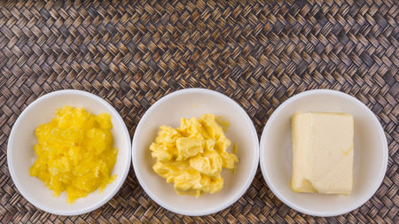 ghee: A block of butter, margarine and ghee in white bowls over wicker background Stock Photo