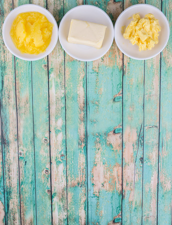 clarified: A block of butter, margarine and ghee in white bowls over rustic wooden background