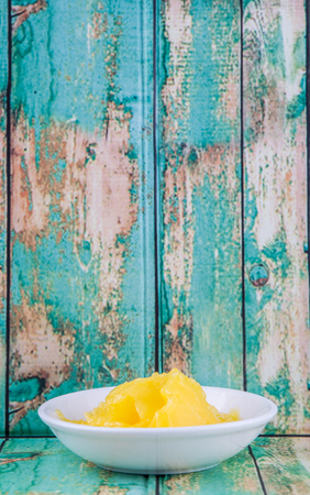 clarified: A bowl of Indian ghee in white bowl over wooden background