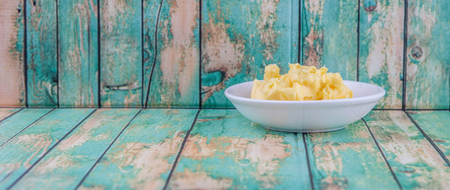 margarine: A bowl of margarine in white bowl over wooden background Stock Photo