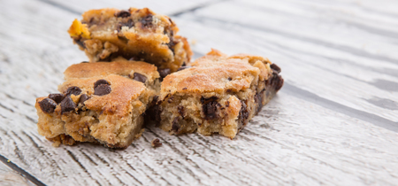blondie: Sweet brownie dessert bar with chocolate chips over wooden background Stock Photo