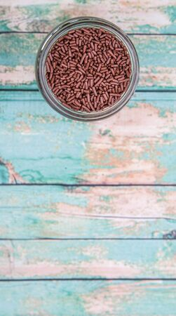 sprinkle: Chocolate sprinkle confetti in a mason jar over rustic aged wooden background
