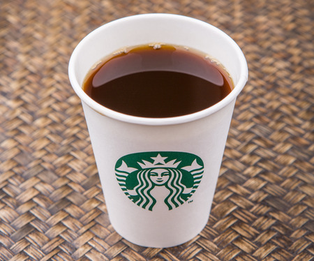starbucks coffee: PUTRAJAYA, MALAYSIA - JULY 20TH, 2015. Starbucks coffee over wicker background. Founded in 1971, Starbucks is the largest coffeehouse company in the world.