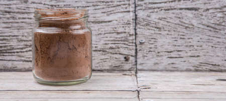 calorie rich food: Brown pure cocoa powder in a mason jar over rustic wooden background