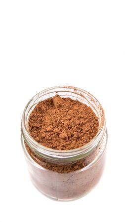 rich flavor: Brown pure cocoa powder in a mason jar over white background Stock Photo