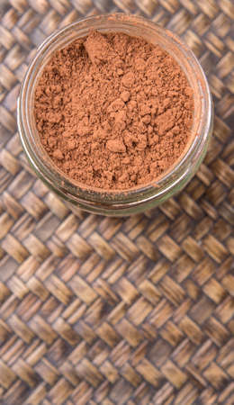 calorie rich food: Brown pure cocoa powder in a mason jar over wicker background