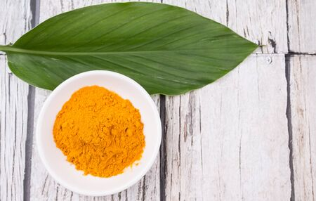 peppery: Turmeric powder and turmeric leaves over rustic wooden background