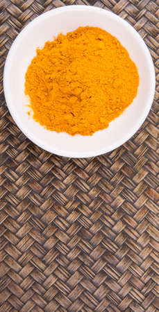 peppery: Turmeric powder in white bowl over wicker background