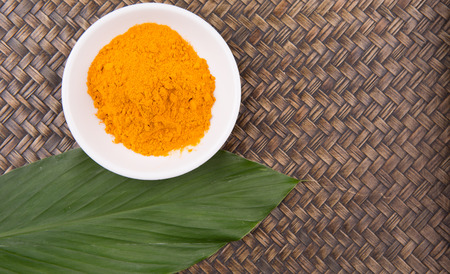 peppery: Turmeric powder and turmeric leaves in white bowl over wicker background