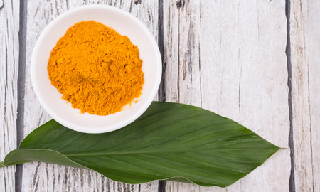 Turmeric powder and turmeric leaves over rustic wooden background