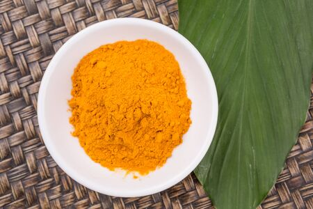 curcumin: Turmeric powder and turmeric leaves in white bowl over wicker background