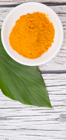 curcumin: Turmeric powder and turmeric leaves over rustic wooden background