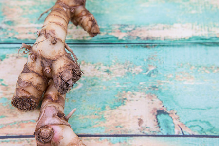 galangal: Galangal or Lengkuas roots over wooden background Foto de archivo