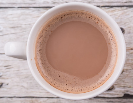 hot beverage: A mug of hot chocolate over wooden background