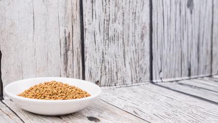 methi: Fenugreek seeds in white bowl over wooden background