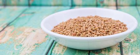 fenugreek: Fenugreek seeds in white bowl over wooden background