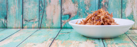 smells: Deep fried shallots for garnishing in white bowl over wooden background