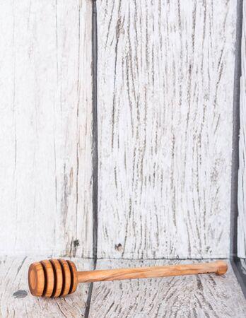 wooden stick: Wooden honey dipper over wooden background